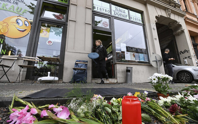 Flowers and candles lie in memory of the victim of a right-wing shooting attack in 2019 in front of the kebab shop where killing took place, in Halle, Germany, October 9, 2020. (Hendrik Schmidt/dpa via AP)