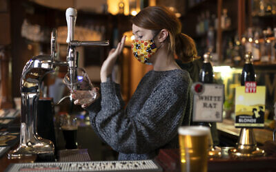 A member of staff pours a drink, at the Dispensary pub in Liverpool, England, Oct 12, 2020 (AP Photo/Jon Super)