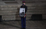 A Republican Guard holds a portrait of Samuel Paty in the courtyard of the Sorbonne university during a national memorial event, Wednesday, Oct. 21, 2020 in Paris. (AP Photo/Francois Mori, Pool)