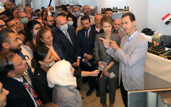 In this photo provided by the official Facebook page of the Syrian Presidency, Syrian President Bashar Assad, right, and first lady Asma Assad, center right, speak during a visit to the Producers exhibition, in Damascus, Syria, Nov. 4, 2020 (Syrian Presidency Facebook page via AP)