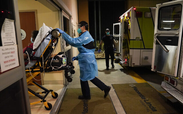 FILE: In this Jan. 8, 2021, file photo, emergency medical technician Thomas Hoang, 29, of Emergency Ambulance Service, pushes a gurney into an emergency room to drop off a COVID-19 patient in Placentia, Calif. (AP Photo/Jae C. Hong, File)