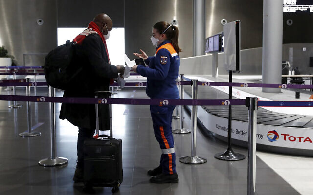 A member of Civil Protection checks air travellers documents at Paris Charles de Gaulle airport in Roissy, near Paris, February 5, 2021. (Gonzalo Fuentes/Pool via AP)