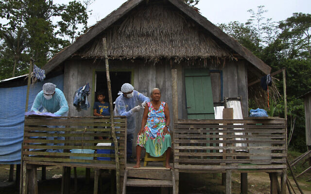 Maria Castro de Lima, 72, receives a dose of the Oxford-AstraZeneca COVID-19 vaccine from a healthcare worker, while sitting on the porch of her home in the Recanto community, along the Purus River, in the Labrea municipality, Amazonas state, Brazil,  Feb. 12, 2021. (AP Photo/Edmar Barros)