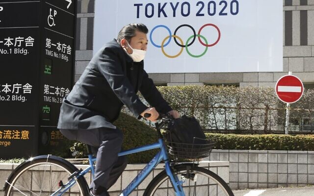 A man wearing a face mask cycles past the logo of the Tokyo Olympics, in Tokyo, Wednesday, Feb. 17, 2021 (AP Photo/Koji Sasahara)