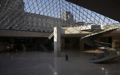 A man walks through the deserted Louvre museum, in Paris, Thursday, Feb. 11, 2021 (AP Photo/Thibault Camus)