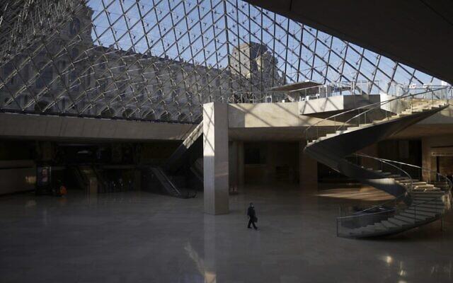 A man walks through the deserted Louvre museum, in Paris, Thursday, Feb. 11, 2021 (AP Photo/Thibault Camus)