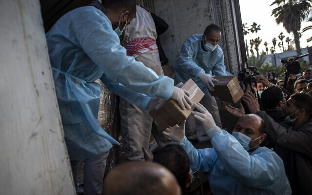 Palestinian workers unload a truck from 20,000 doses of Russian-made Sputnik V vaccine upon its arrival to Gaza Strip, at the Rafah crossing border with Egypt, February 21, 2021. (Khalil Hamra/AP)