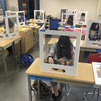 Socially distanced and with protective partitions students work on an art project during class at the Sinaloa Middle School in Novato, California on March 2, 2021 (AP Photo/Haven Daily)