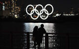 A man and a woman stand with the backdrop of the Olympic rings floating in the water in the Odaiba section in Tokyo, March 3, 2021. (AP Photo/Eugene Hoshiko)