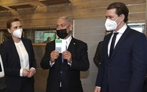 Israeli Prime Minister Benjamin Netanyahu, center, holds a Green Pass for citizens vaccinated against COVID-19, as he visits a fitness gym with Austrian Chancellor Sebastian Kurz, right, and Danish Prime Minister Mette Frederiksen, to observe how the pass is used, in Modi'in, Thursday, March 4, 2021 (Avigail Uzi/Pool via AP)