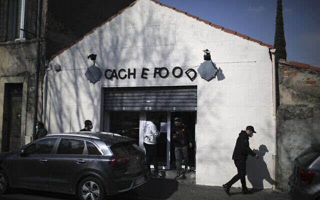 People gather outside a kosher market after a man visibly brandished a knife outside a Jewish school and a kosher market in Marseille, southern France, Friday, March 5, 2021 (AP Photo/Daniel Cole)