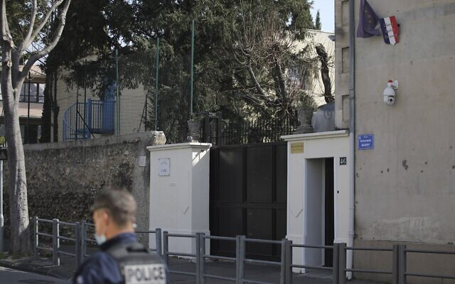 A police officer guards a Jewish school after a man visibly brandished a knife outside a Jewish school and a kosher market in Marseille, southern France, Friday, March 5, 2021 (AP Photo/Daniel Cole)