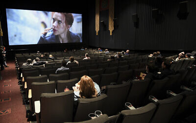 Moviegoers sitting in a socially distant seating arrangement at the AMC Lincoln Square 13 theater on the first day of reopened theaters after being closed due to the COVID-19 pandemic, March 5, 2021, in New York. (Evan Agostini/Invision/AP)