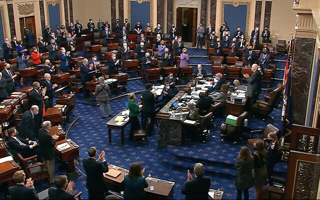 In this image from video, senators stand and applaud support staff, before the final vote on the Senate version of the COVID-19 relief bill in the Senate at the US Capitol in Washington, March 6, 2021. (Senate Television via AP)