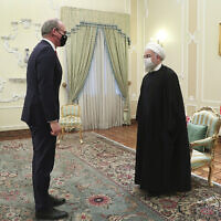 Iranian President Hassan Rouhani, right, and Irish Foreign Minister Simon Coveney greet at the start of their meeting in Tehran, Iran, March 7, 2021. (Iranian Presidency Office via AP)