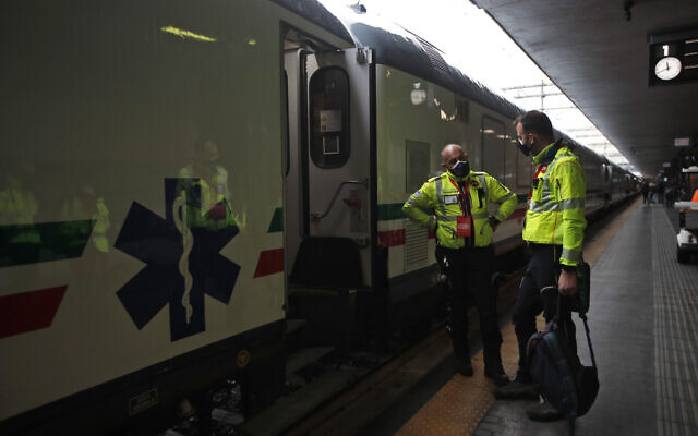 Medical personnel stand outside a train adapted to treat patients, unveiled to the press in Rome Termini central station, March 8, 2021. The health train allows patients to be transferred and treated in eight carriages equipped with specific equipment, including intensive care spaces. (AP Photo/Alessandra Tarantino)