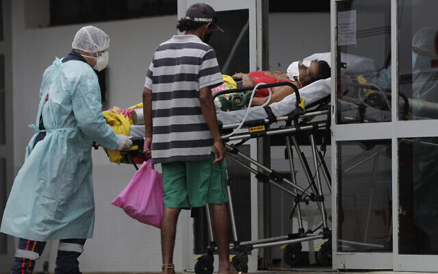 Healthcare workers receive a patient suspected of having COVID-19 at the public HRAN Hospital in Brasilia, Brazil, March 8, 2021. (Eraldo Peres/AP)