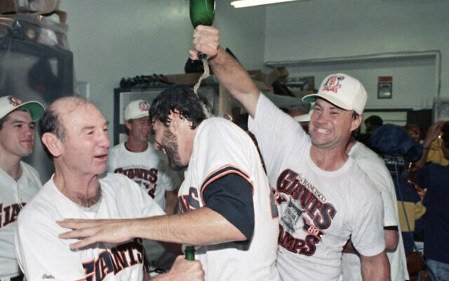 FILE - In this Oct. 9, 1989, file photo, San Francisco Giants catcher Terry Kennedy, right, pours sparkling wine over the head of Steve Bedrosian, center, as pitching coach Norm Sherry watches at left following the Giants' victory over the Chicago Cubs to secure the National League pennant in San Francisco (AP Photo/Eric Risberg, File)