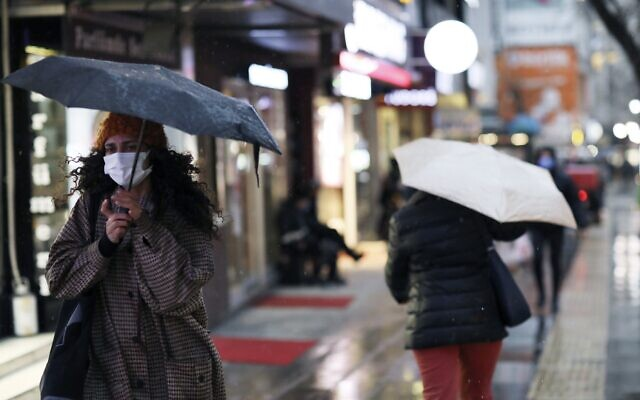 A woman wearing a mask to protect against the spread of coronavirus walks in the rain, in Ankara, Turkey, Tuesday, March 16, 2021 (AP Photo/Burhan Ozbilici)