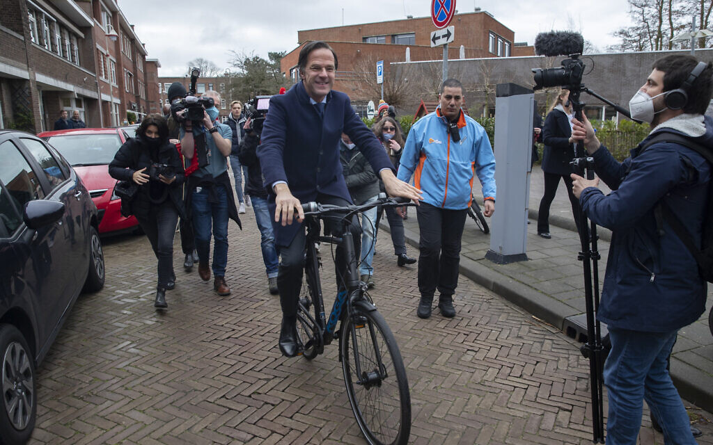 Dutch caretaker Prime Minster Mark Rutte leaves on his bicycle after casting his vote in a general election in The Hague, Wednesday, March 17, 2021. (AP Photo/Peter Dejong)