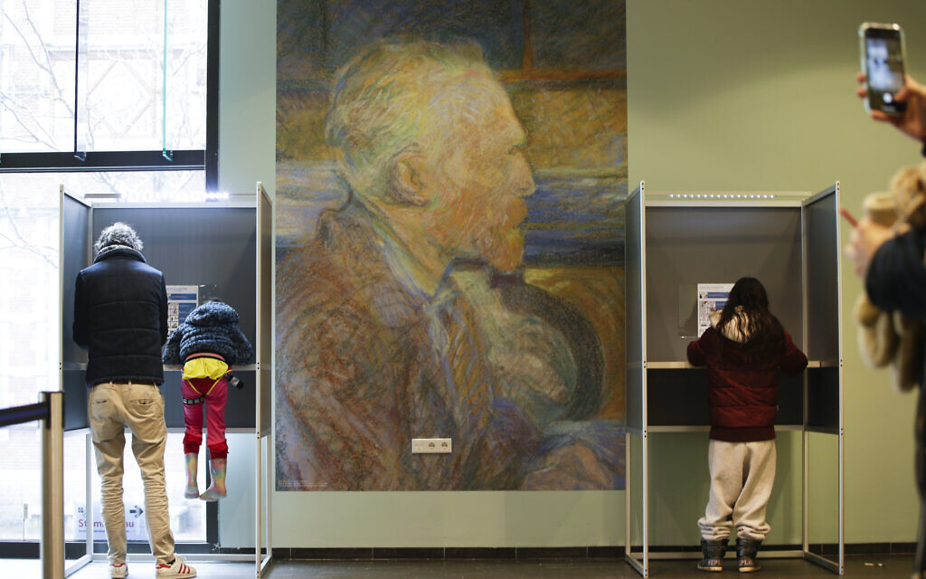 A mother uses her mobile phone to take an image of her husband and child in a voting booth, left, prior to casting their ballot for a general election at the Van Gogh Museum in Amsterdam, Netherlands, Wednesday, March 17, 2021. (AP Photo/Peter Dejong)