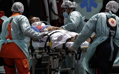 Healthcare workers take on a stretcher a patient suspected of having COVID-19 from an ambulance, at the HRAN public hospital in Brasilia, Brazil, March 23, 2021 (AP Photo/Eraldo Peres)