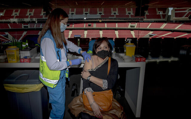 A woman receives a dose of the AstraZeneca vaccine, during a mass vaccination campaign at Wanda Metropolitano stadium in Madrid, Spain, March 24, 2021 (AP Photo/Manu Fernandez)