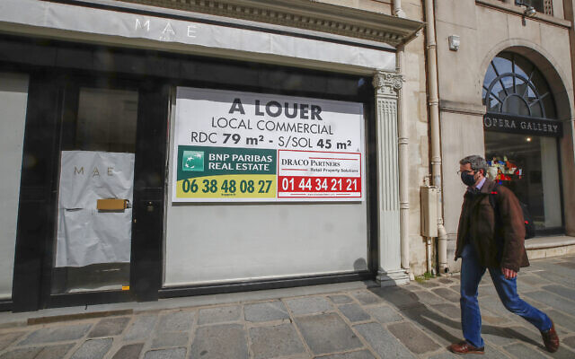 A man wearing a mask to prevent the spread of the coronavirus walks past a vacant boutique for rent in Paris,  March 25, 2021 (AP Photo/Michel Euler)