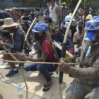 Anti-coup protesters prepare makeshift bow and arrows to confront police in Thaketa township Yangon, Myanmar, March 27, 2021 (AP Photo)