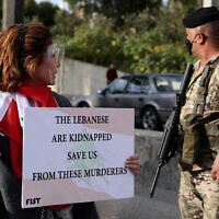 An anti-government protester holds a placard, as she looks at a Lebanese army soldier, during a protest against the political leadership they blame for the economic and financial crisis, near the presidential palace in Baabda, east of Beirut, Lebanon, March. 27, 2021. (Bilal Hussein/AP)