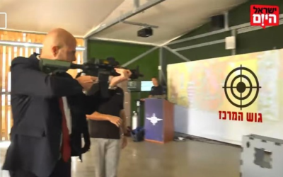 Justice Minister Amir Ohana shoots at a target labeled 'the center bloc,' in an interview with the Israel Hayom newspaper on March 19, 2021. (screenshot: Facebook)