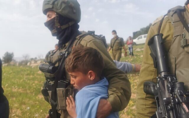 IDF soldiers arrest Palestinian children picking spices in a West Bank field on March 10, 2021. (B'Tselem)
