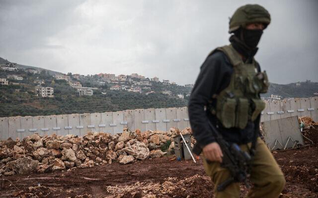 An IDF soldier walks near the border fence with Lebanon, near the northern Israeli city of Metula, on December 24, 2018. (Hadas Parush/Flash90)