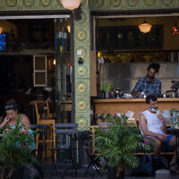 Israelis wear protective facemasks as they sit in a cafe in Tel Aviv, July 8, 2020. (Miriam Alster/FLASH90)