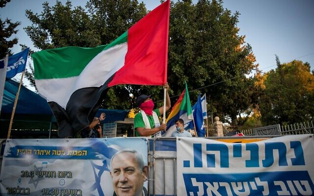 A man waves a giant United Arab Emirates flag outside the Prime Minister's official residence in Jerusalem on August 19, 2020. (Yonatan Sindel/Flash90)