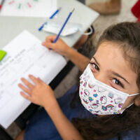 A child wearing a face mask at the Kramim school in Jerusalem on November 1, 2020. (Olivier Fitoussi/Flash90)