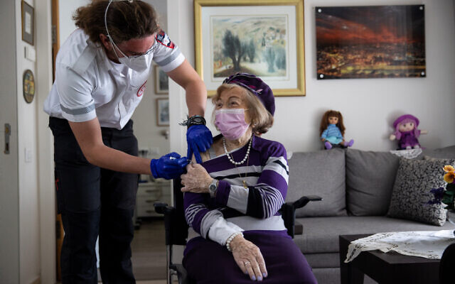 Illustrative: A Magen David Adom worker administers a COVID-19 vaccine to Holocaust survivor Yaffa Balaban, 95, at her apartment in Beit Tovei Hair retirement residence in Jerusalem on January 26, 2021. (Yonatan Sindel/Flash90)