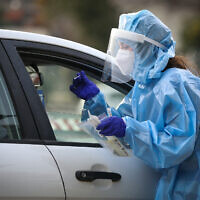 A medical worker collects samples for coronavirus testing in Safed, on February 8, 2021 (David Cohen/Flash90)
