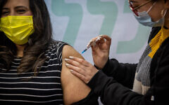 A Israeli woman receives a vaccination in Jerusalem, on February 15, 2021. (Yonatan Sindel/Flash90)