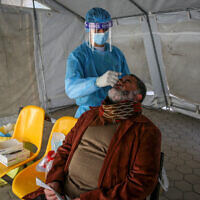 Palestinian Health worker takes samples for coronavirus at a health center in Rafah, in the southern Gaza Strip, on February 16, 2021. (Abed Rahim Khatib/Flash90)