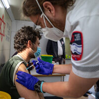 An Israeli man receives a COVID-19 vaccine shot at a mobile Magen David Adom vaccination station at the Mahane Yehuda market in Jerusalem on February 22, 2021. (Olivier Fitoussi/Flash90)