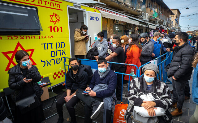 People receive COVID-19 vaccine injections in a mobile Magen David station at the Mahane Yehuda market in Jerusalem on February 22, 2021. (Olivier Fitoussi/Flash90)