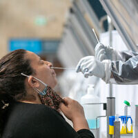 A technician collects nasal swab samples for COVID-19 at the coronavirus lab, at the Ben-Gurion International Airport on February 28, 2021. (Yossi Aloni/Flash90)