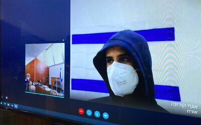Yarin Sherf, suspected of raping 13-year-old girl at a quarantine hotel, is seen on a screen via a video link during a court hearing at the Tel Aviv Magistrate's Court, March 1, 2021. (Avshalom Sassoni/Flash90)