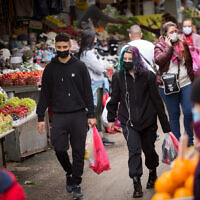 Illustrative: Israelis wear protective face masks as they shop at the Carmel market in Tel Aviv, on March 1, 2021. (Miriam Alster/FLASH90)