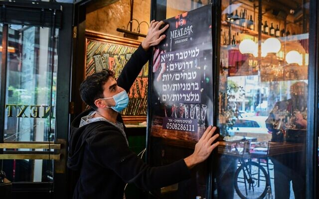 A worker at a restaurant in Tel Aviv hangs a 'help wanted' sign on the window, on March 3, 2021. (Avshalom Sassoni/Flash90)