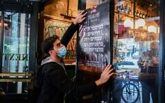 Worker puts up a poster advertising for staff at a restaurant in Tel Aviv, on March 3, 2021 (Avshalom Sassoni/Flash90)