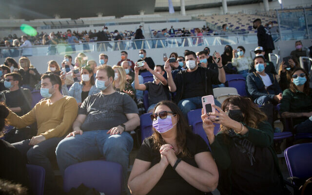 People enjoy artist Ivri Lieder at a concert organized by the Tel Aviv municipality at Bloomfield Stadium, March 5, 2021 (Miriam Alster/FLASH90)