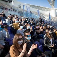 Israeli Green Pass holders enjoy singer Ivri Lieder at a concert organized by the Tel Aviv municipality, at Bloomfield Stadium, March 5, 2021. (Miriam Alster/FLASH90)