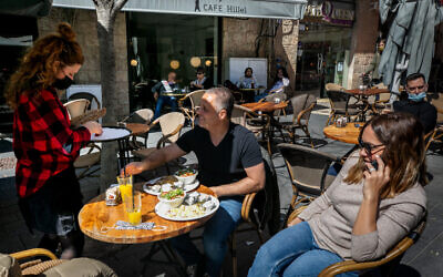 Customers sit at a cafe  in Jerusalem on March 7, 2021. (Olivier Fitoussi/Flash90)
